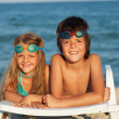 Kids laying on beach chair wearing swimming goggles — Stock Photo #44494157