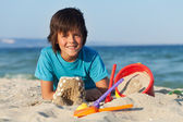 Boy building sand castles on the sea shore — Stockfoto