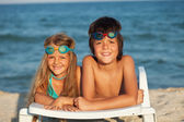 Kids laying on beach chair wearing swimming goggles — Stock Photo