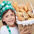 Happy baker boy holding basket with fresh bakery products — Stock Photo #45241283
