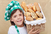 Happy baker boy holding basket with fresh bakery products — Stock Photo