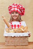 Little chef offering bakery products — Stock Photo