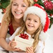Merry christmas - woman and little girl with a present — Stock Photo #6410924