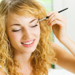 Blond woman with makeup brush at home — Stock Photo #12035711