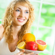 Cheerful smiling blond woman with fruits — Stock Photo