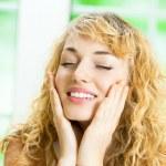 Happy smiling woman applying creme, indoor — Stock Photo