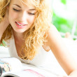 Cheerful blond woman reading magazine — Stock Photo #12036448