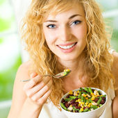 Happy smiling young woman eating salad — Stock Photo