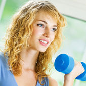 Young happy smiling woman with dumbbell, indoors — Stock Photo
