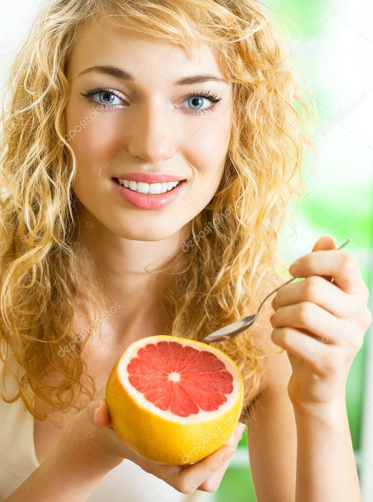 Cheerful blond woman eating grapefruit  Stock Photo #12036391