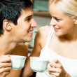 Cheerful couple with cups of coffee, indoor - Stock Photo