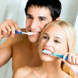 Cheerful young couple cleaning teeth together — Stock Photo #12156414