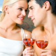 Stock Photo: Cheerful couple with glasses of redwine