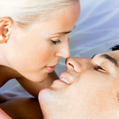 Young kissing cheerful attractive couple — Stock Photo