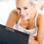 Cheerful woman with laptop, at home — Stock Photo