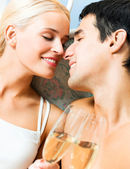 Cheerful couple with glasses of champagne — Stock Photo