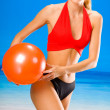 Young woman playing with ball on beach — Stock Photo