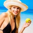 Young happy woman with apple on beach — Stock Photo #12280736