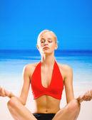 Woman doing yoga exercises or meditating — Stock Photo