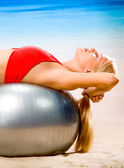Woman doing exercises with ball on beach — Stock Photo
