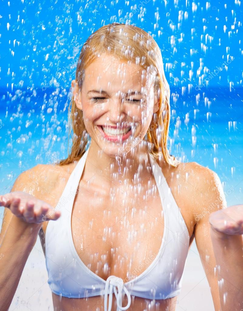 Young beautiful happy tanned blond woman in bikini at rain or summer shower on beach — Stock Photo #12280825