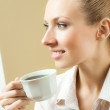Young woman drinking coffee or tea, at home — Stock Photo #12413504