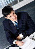 Young businessman writting at office — Stock Photo