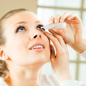 Woman dripping eye with eyes drops — Stockfoto