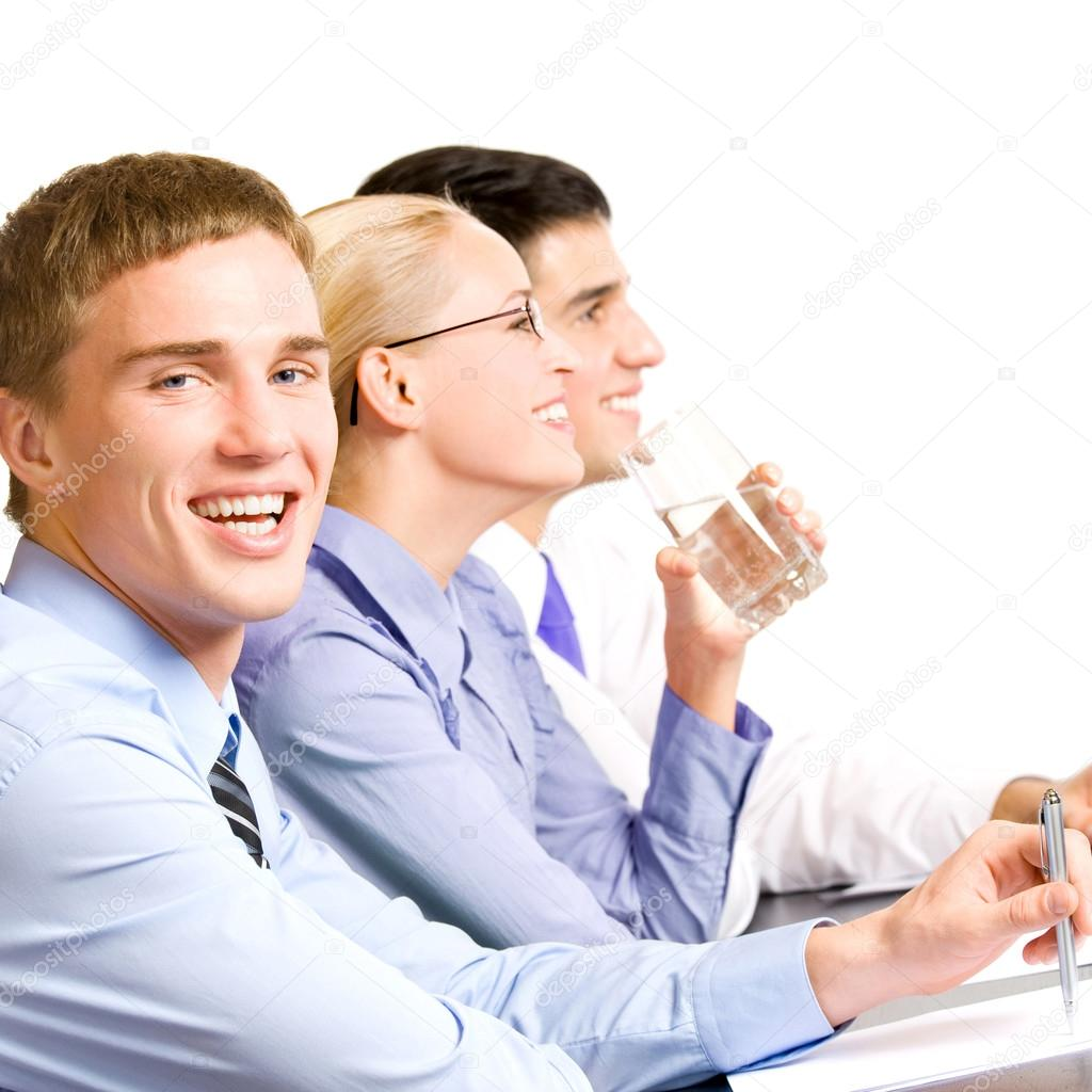 Three young happy smiling businesspeople at meeting, presentation or conference, isolated over white background — Stock Photo #12412576