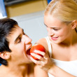 Cheerful couple eating apple together — Stock Photo #12570372