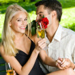Young couple with gifts, rosa and champagne, outdoor — Stock Photo #12579770