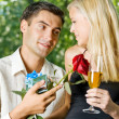 Young couple with gifts, rosa and champagne, outdoor — Stock Photo #12579779