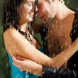 Young couple hugging under a rain — Stock Photo #12579966