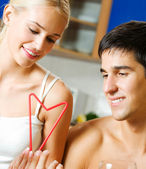 Cheerful couple celebrating with heart symbol, indoors — Stock Photo