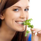 Cheerful woman eating potherbs, over white — Stock Photo