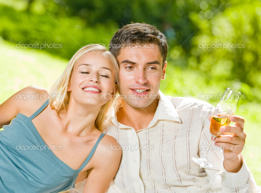 Young happy smiling cheerful attractive couple celebrating with glasses of champagne, outdoor — Stock Photo #12579813