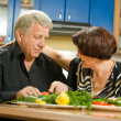 Stock Photo: Cheerful senior couple cooking at home