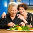 Cheerful senior couple cooking at home - Stock Photo