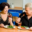 Cheerful senior couple eating at home together — Stock fotografie #12587495