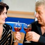 Cheerful senior couple toasting with redwine — Stock Photo