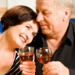 Stock Photo: Cheerful senior couple toasting with redwine