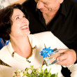 Cheerful senior couple with gifts indoor - Stock Photo