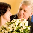 Cheerful senior couple with roses indoor — Stock Photo