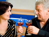 Cheerful senior couple toasting with redwine — Stock Photo