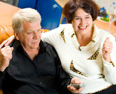 Cheerful senior couple watching TV together — Stock Photo