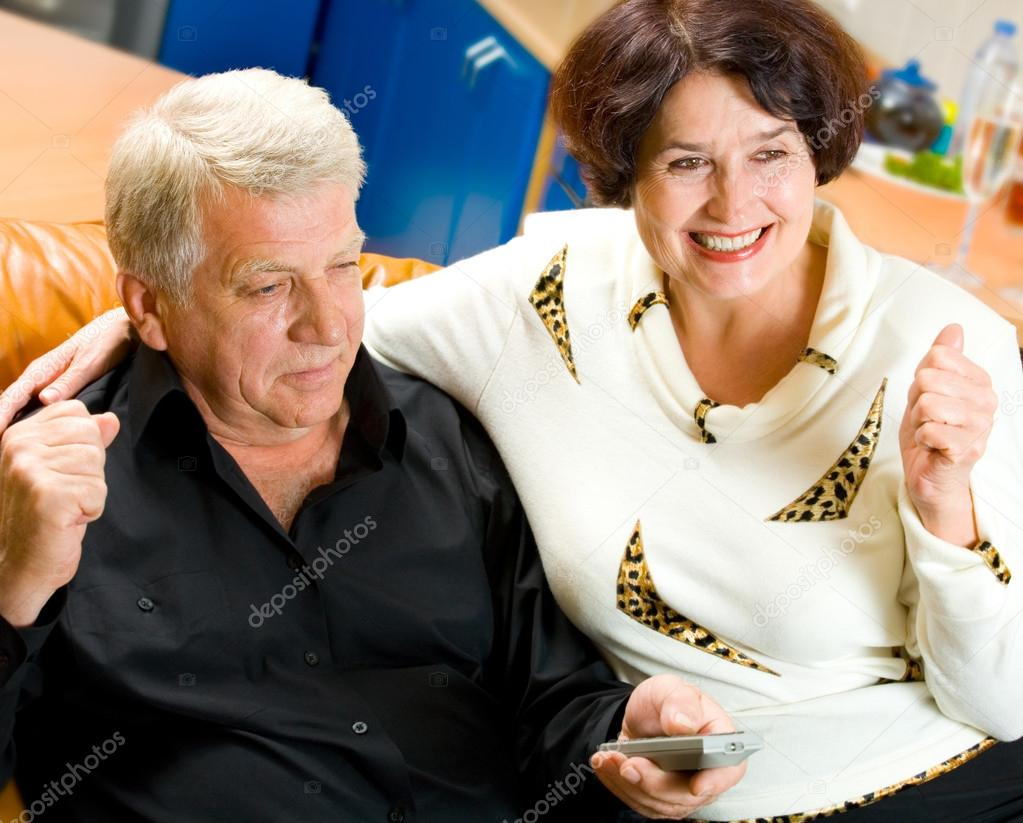 Cheerful senior couple watching TV together  — Stock Photo #12587724