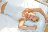 Young woman waking up on bed — Stock Photo