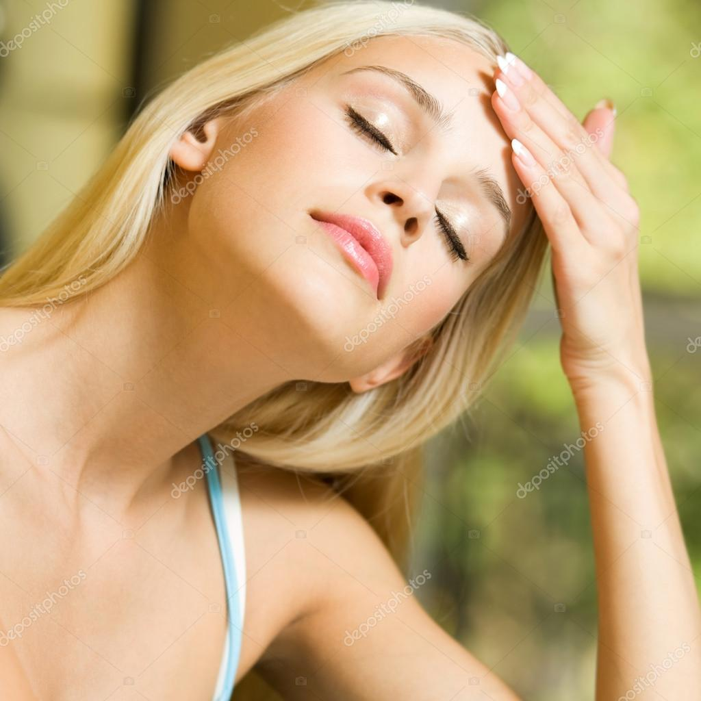 Portrait of young blond woman with headache or applying creme — Stock Photo #12724886