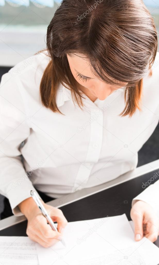 Young businesswoman writing or signing document — Stock Photo #12732381