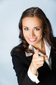 Business woman pointing finger at viewer, over blue — Stock Photo